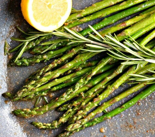 asparagus in a skillet with lemon and rosemary