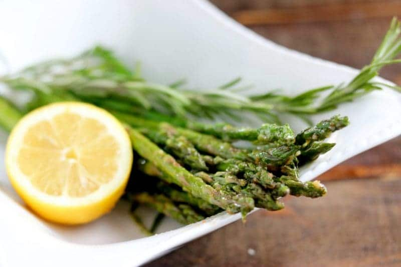 Skillet roasted asparagus with lemon half and rosemary sprig on side in white serving bowl on wood table.