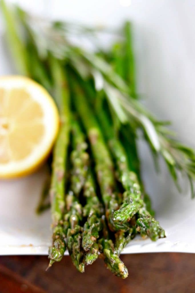 Closeup of skillet roasted asparagus garnished with rosemary sprig and lemon half on side on white plate.