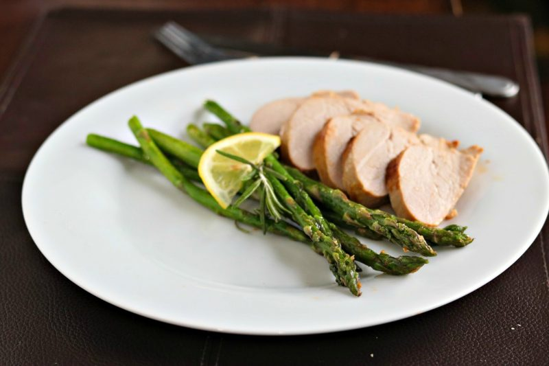 Skillet roasted asparagus with pork tenderloin medallions on white plate on wood table.