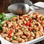 white bean salad in a white bowl with utensils