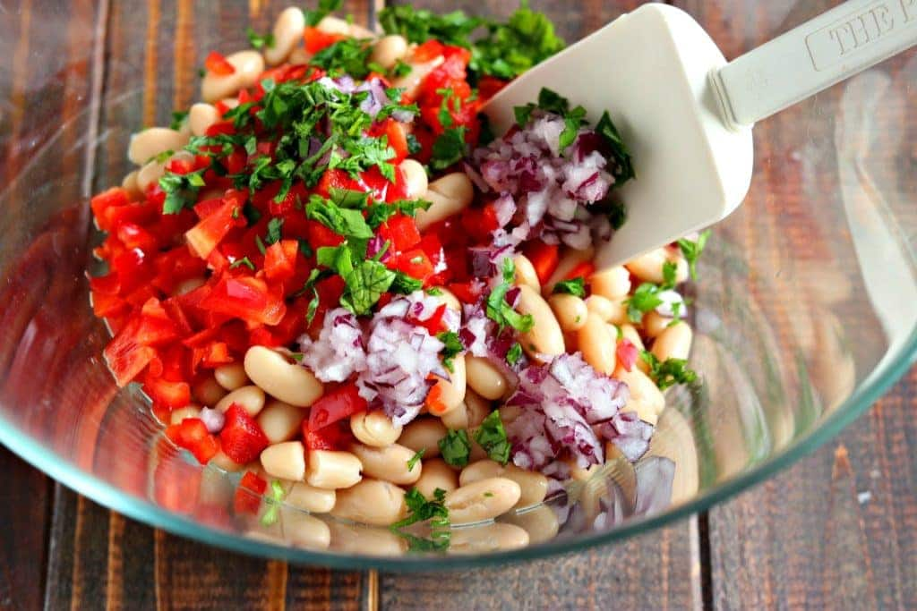 mixing the ingredients for white bean salad in clear bowl with a spatula