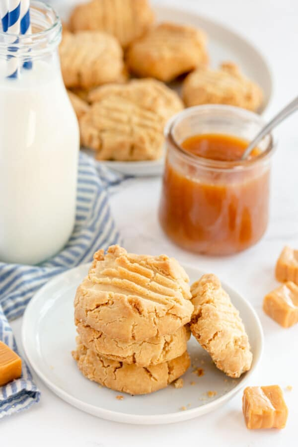 caramel cookies on a white plate with a bottle of milk