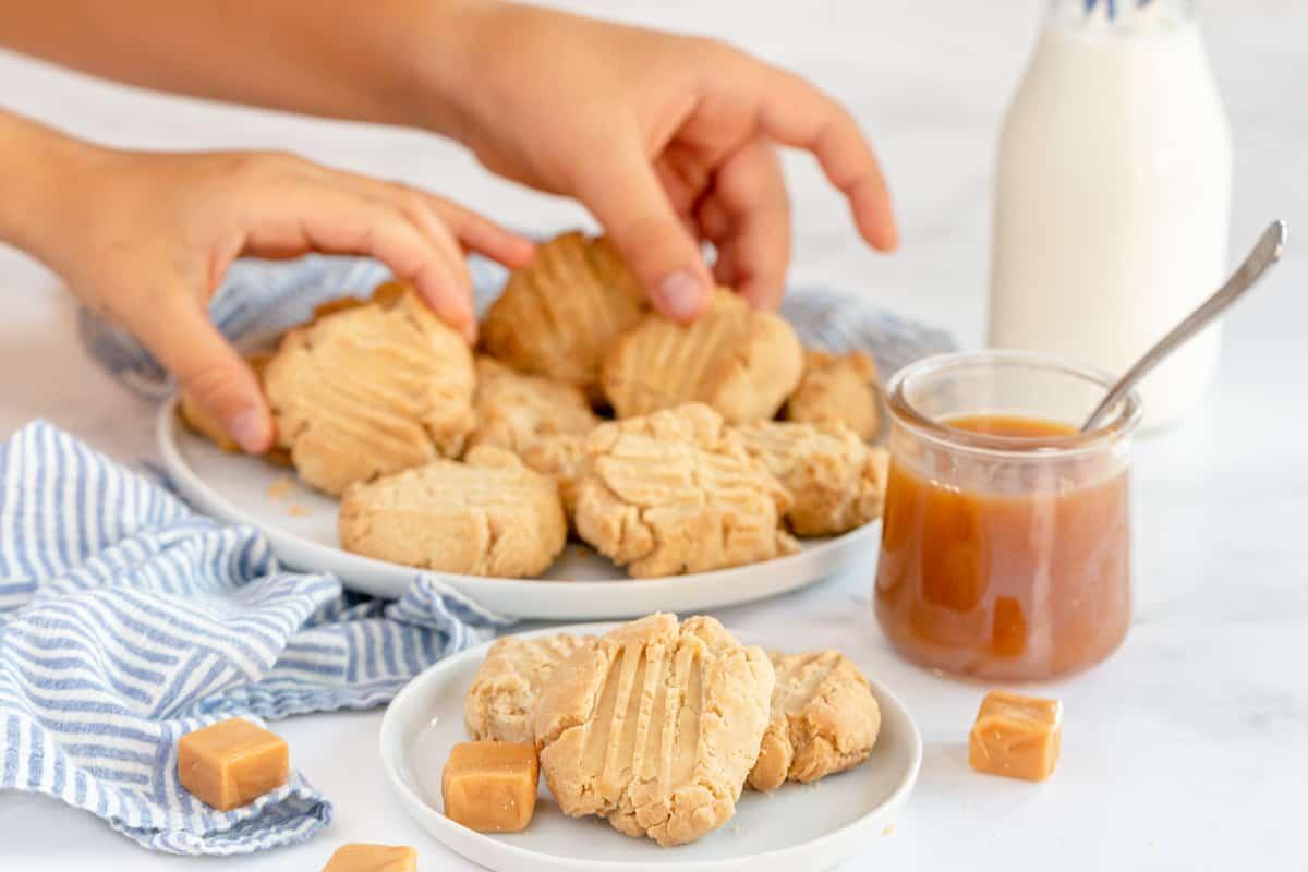 hands grabbing caramel cookies off a plate