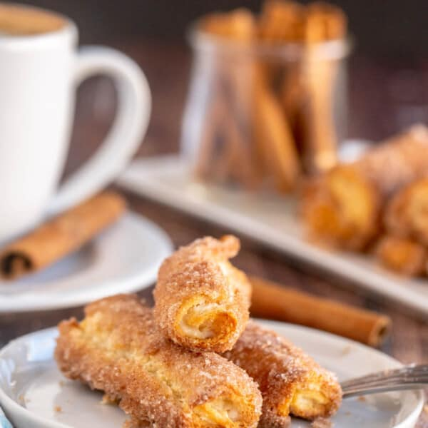 cinnamon cream cheese roll ups on a white plate with a coffee cup