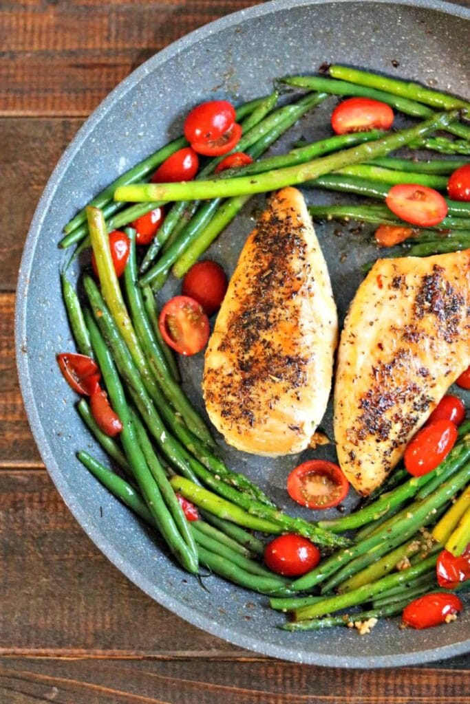 Overhead shot of chicken provencal with green beans, asparagus, and halved grape tomatoes in skillet on wood table.