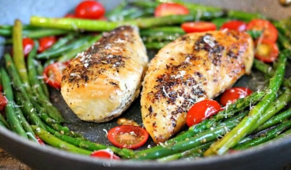 chicken with green beans and tomatoes in a skillet
