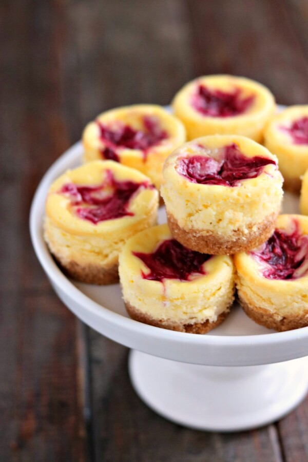mini lemon cheesecakes with berry swirl on a cake stand