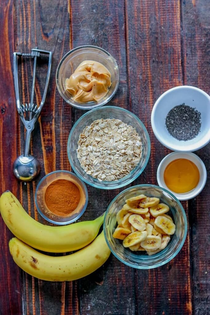 Overhead shot of two bananas, metal melon baller and individual banana oatmeal energy bites ingredients in bowls on wood table.