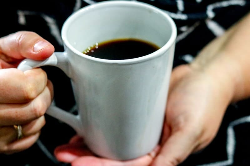 white mug filled with coffee held in hands
