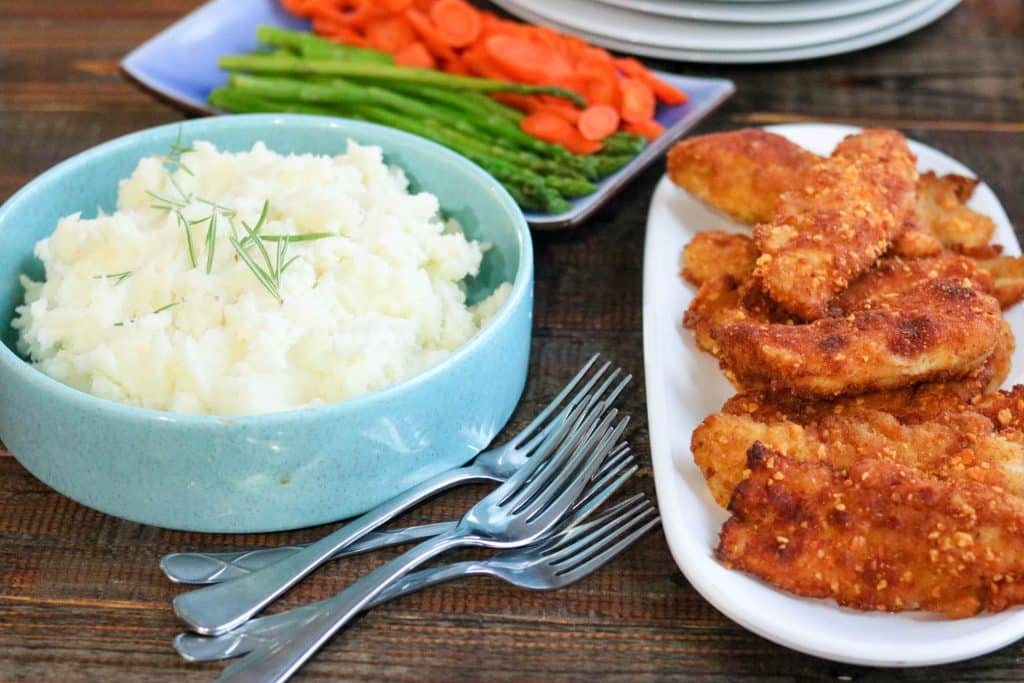 Breaded chicken tenders on white serving plate with mashed potatoes in blue bowl and asparagus spears and carrot slices on blue serving plate on the side on wood table.