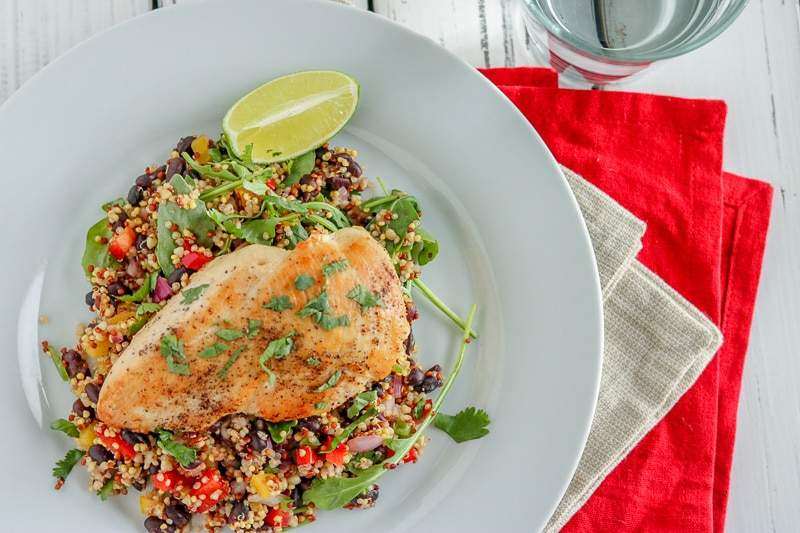quinoa salad with a chicken breast on a white plate and a red napkin