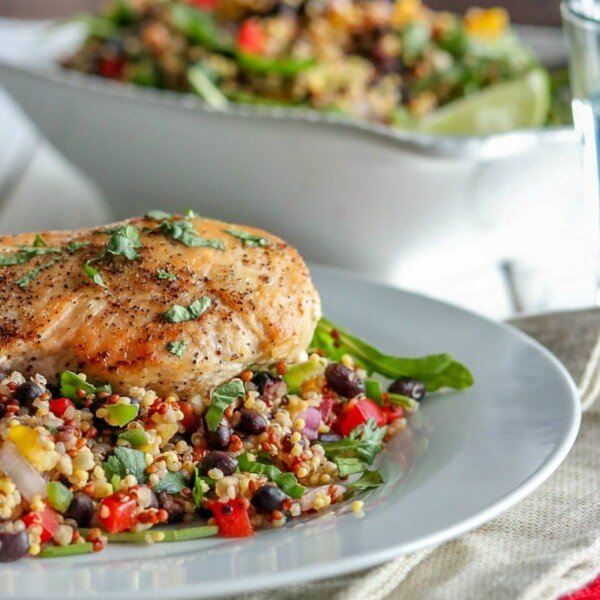 quinoa salad with a chicken breast on a white plate