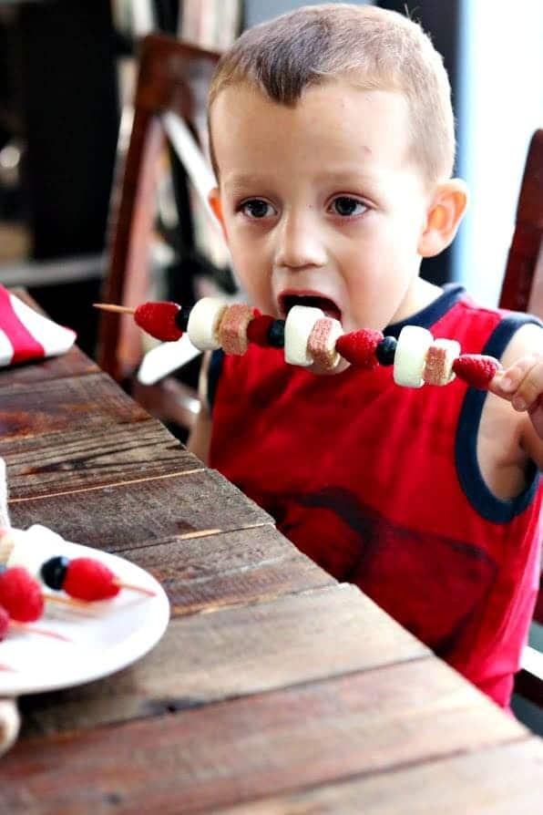 Child eating patriotic cookie kabobs.