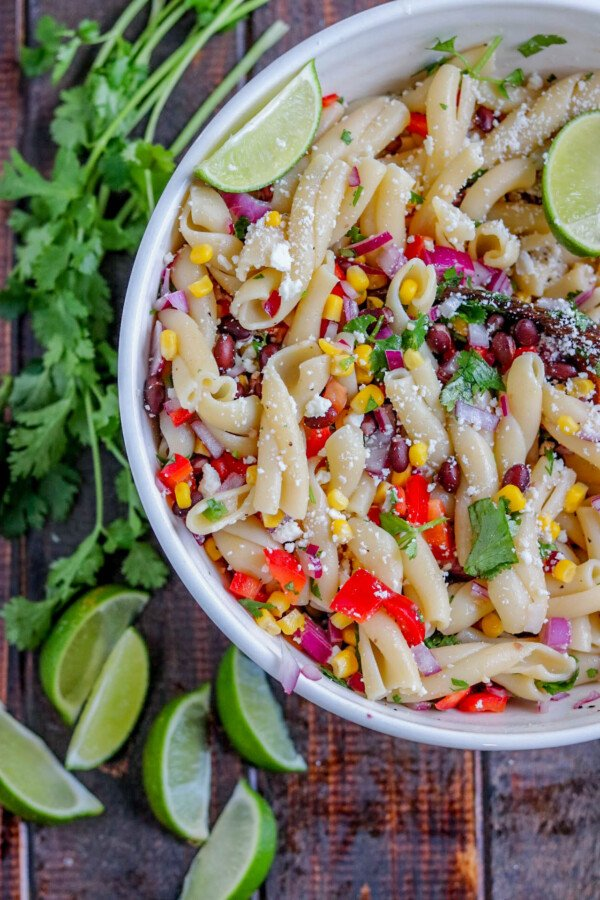 a white bowl of southwestern pasta salad with cilantro and limes