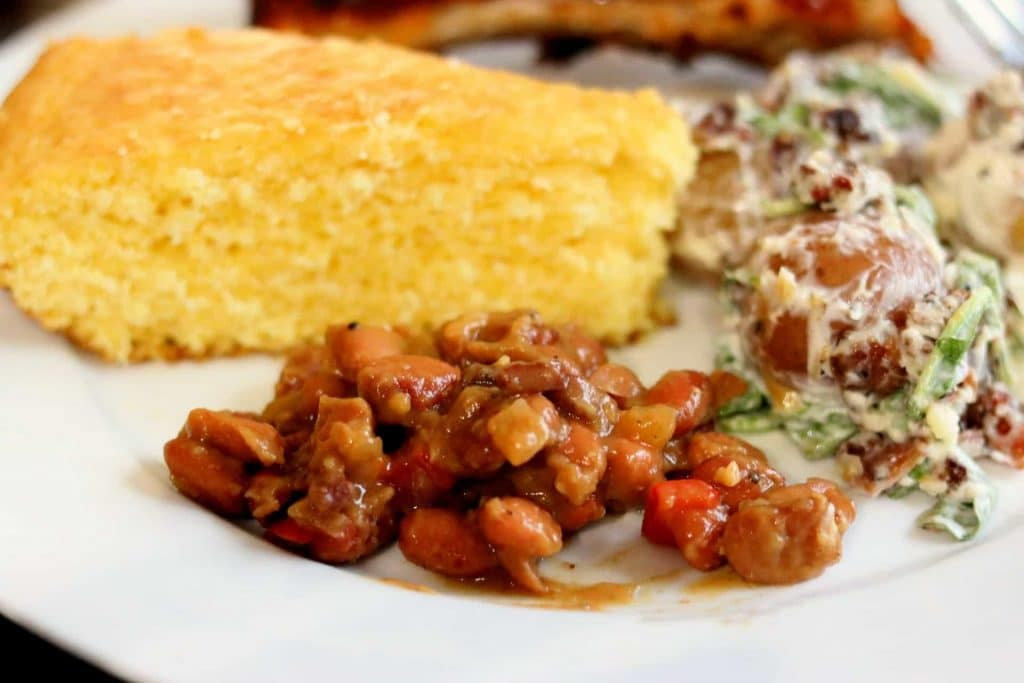 Closeup of cracked pepper steak baked beans with cornbread, potato salad and ribs on a white plate.