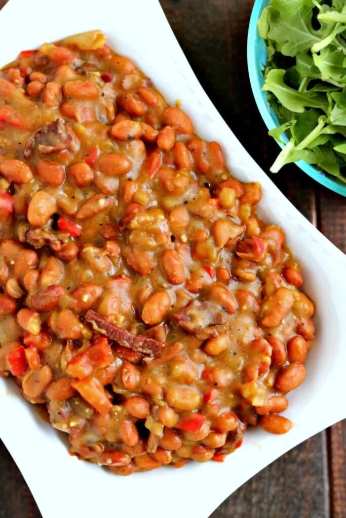 Overhead shot of cracked pepper steak baked beans in white serving bowl with salad in blue bowl on the side on wood table.