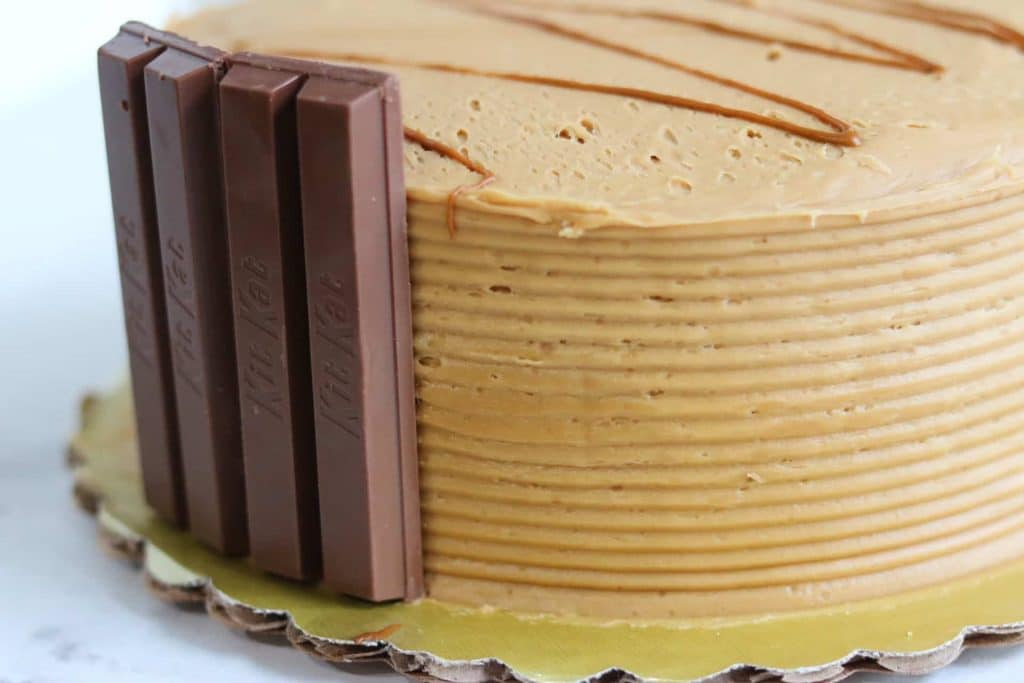 Adding vertical KitKat pieces to the edge of frosted cake.