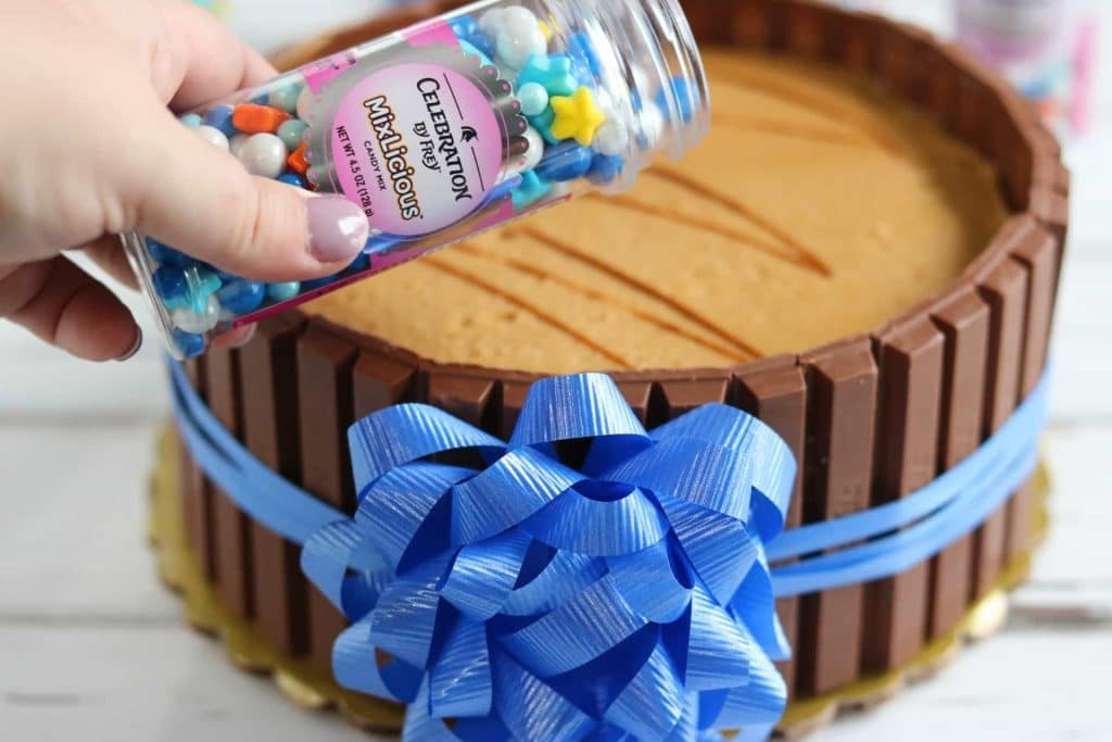 Container of Celebration MixLicious candies over undecorated Celebration KitKat cake with blue ribbon and bow tied around it on white wood table.