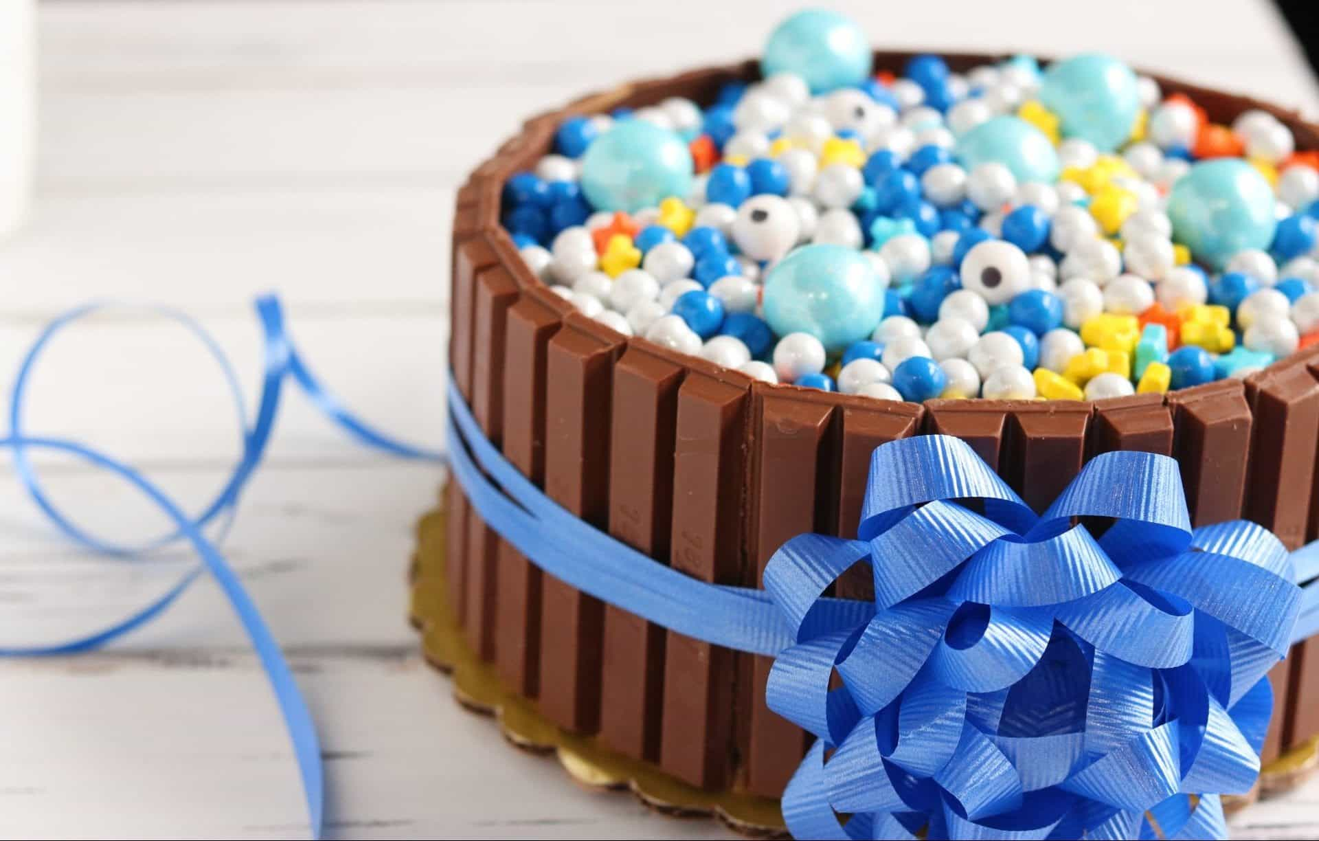 Closeup of celebration KitKat cake with blue ribbon and bow tied around it on white wood table.