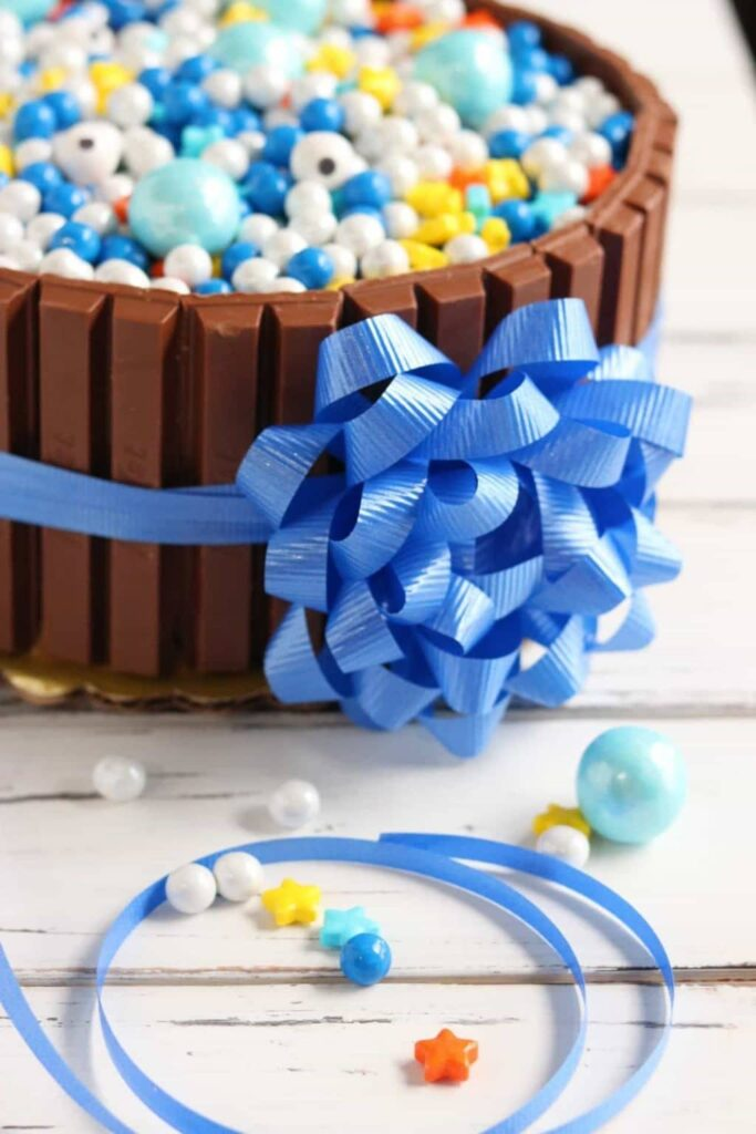 Closeup of celebration KitKat cake with blue ribbon and bow tied around it with more blue ribbon and candy pieces beside it on white wood table.