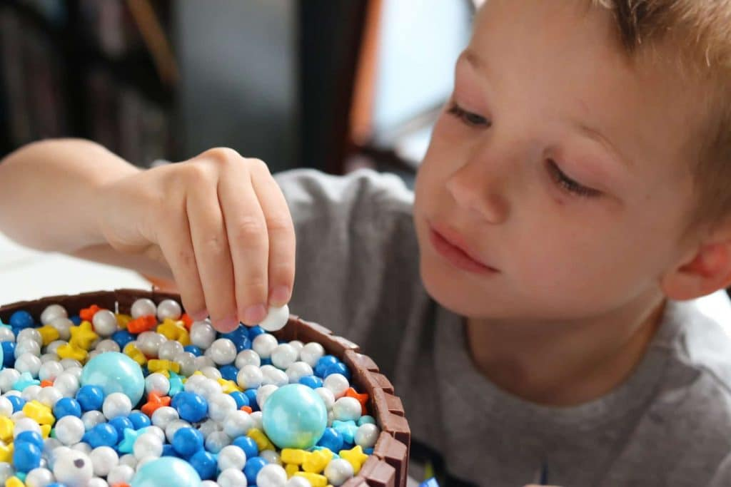 Child adding candy to top of celebration KitKat cake.