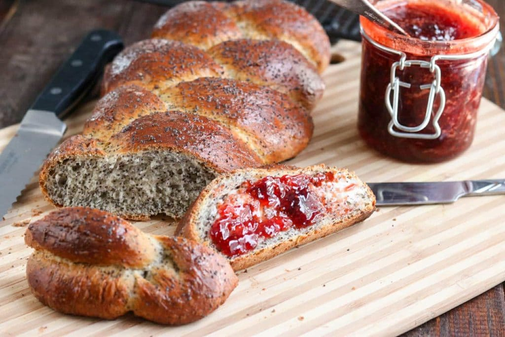 Braided poppy seed loaf with two slices cut and one spread with jam on wood cutting board with bread knife, butter knife, and jar of jam on the side.