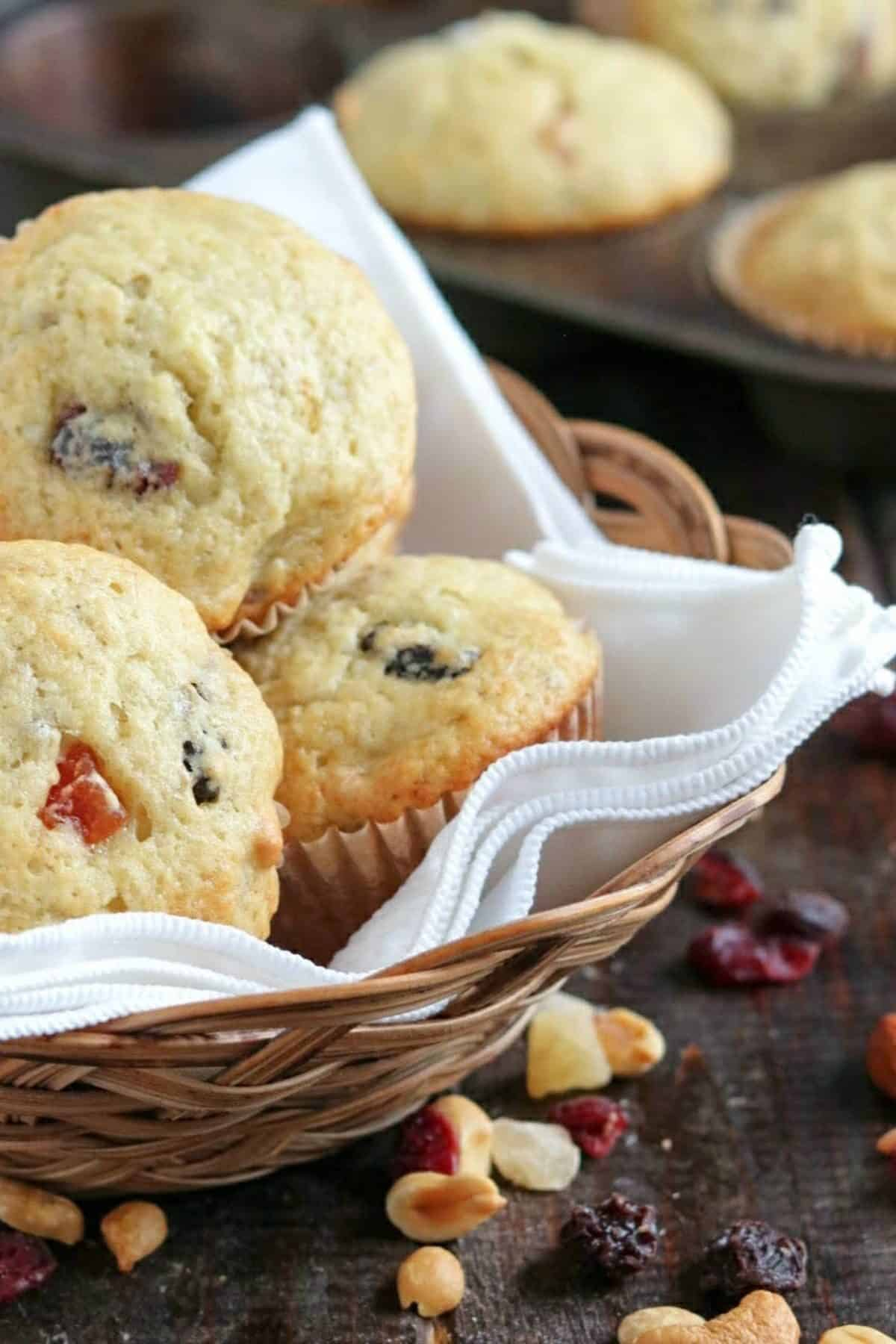 muffins in a basket with fruit/nuts on a wooden board