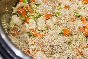 Adding quinoa to chicken stew ingredients.