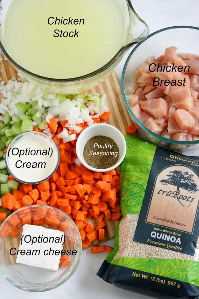 Overhead shot of cutting board with diced carrots, celery, and onions, on wood cutting board with remaining stew ingredients in bowls and tru Roots quinoa package on side.