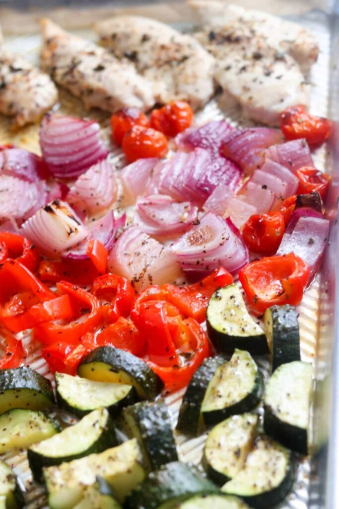 Overhead closeup of roasted zucchini, red pepper, red onion, grape tomatoes, and chicken tenderloins on sheet pan.