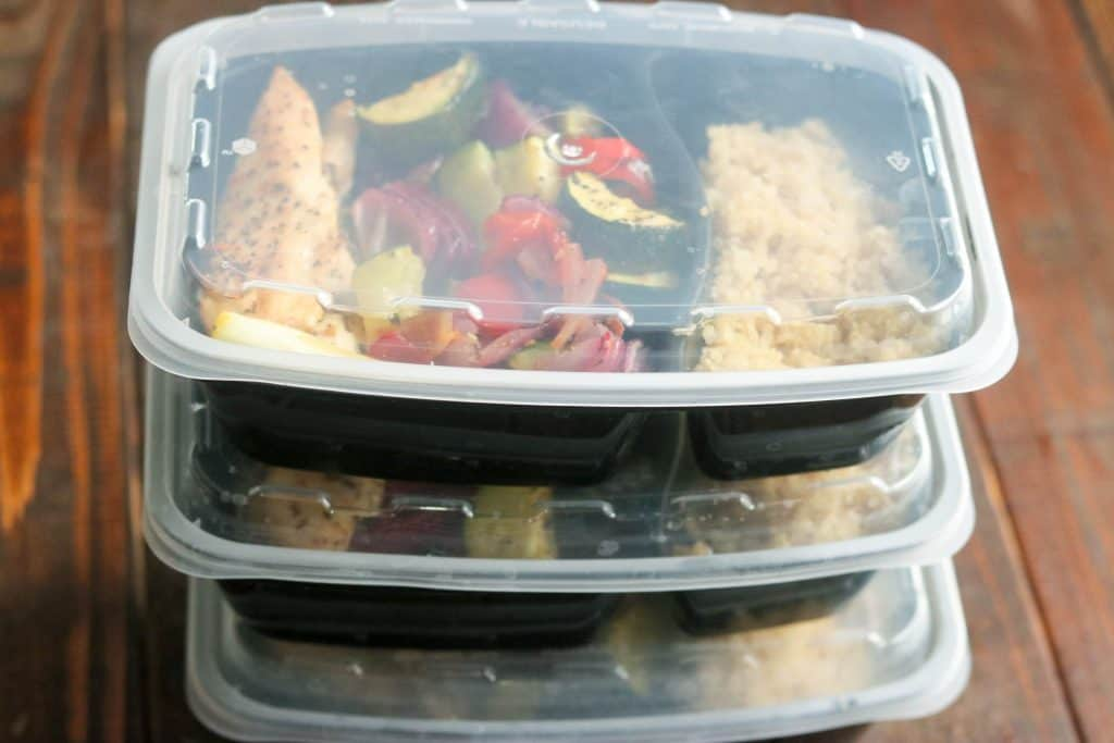 Three resealable containers filled with rice and sheet pan chicken and vegetables stacked up on wood table.