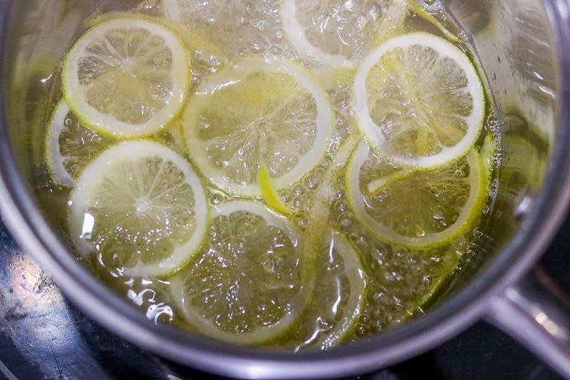 Overhead shot of cooking candied lemon slices in pot.