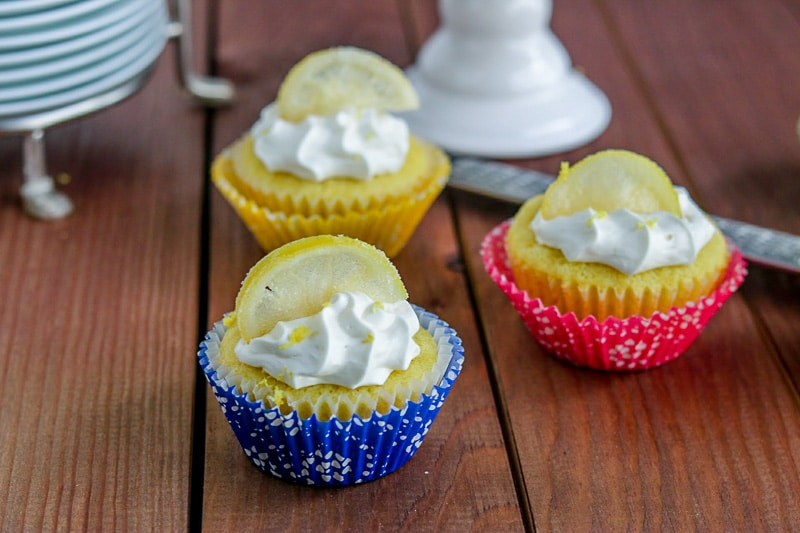 Close up of three lemon olive oil cupcakes with stack of plates and zester in background on wood table.