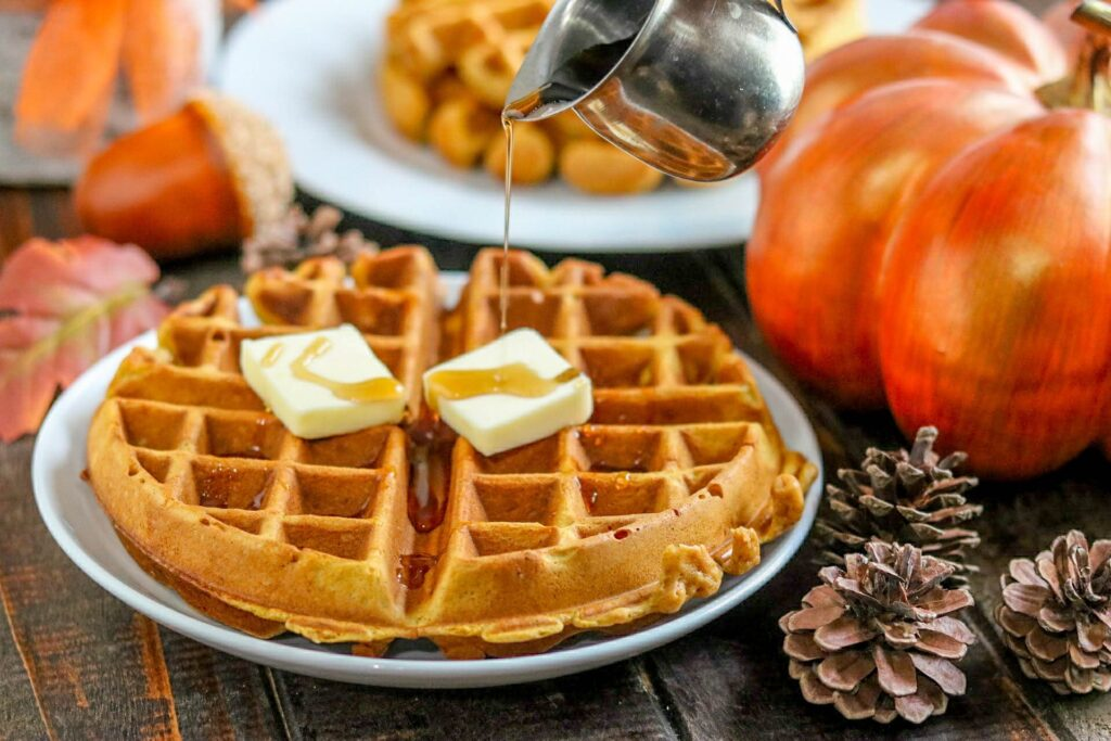 Pumpkin spice waffles on white plate topped with butter pats and being drizzled with syrup surrounded by pumpkin, pine cones, and another plate with waffle on wood table.