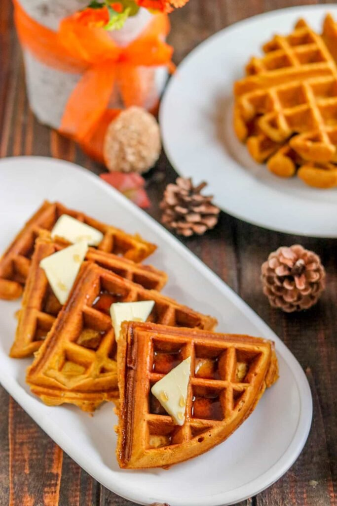 Wedges of pumpkin spice waffles on white plate with another round white plate with waffles, pine cones, and decorative acorn on side on wood table.