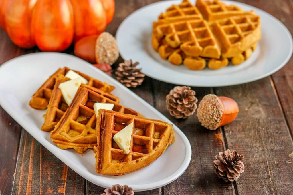Wedges of pumpkin spice waffles on white serving plate surrounded by pumpkin, pine cones, and another round white plate with stack of waffles on wood table.