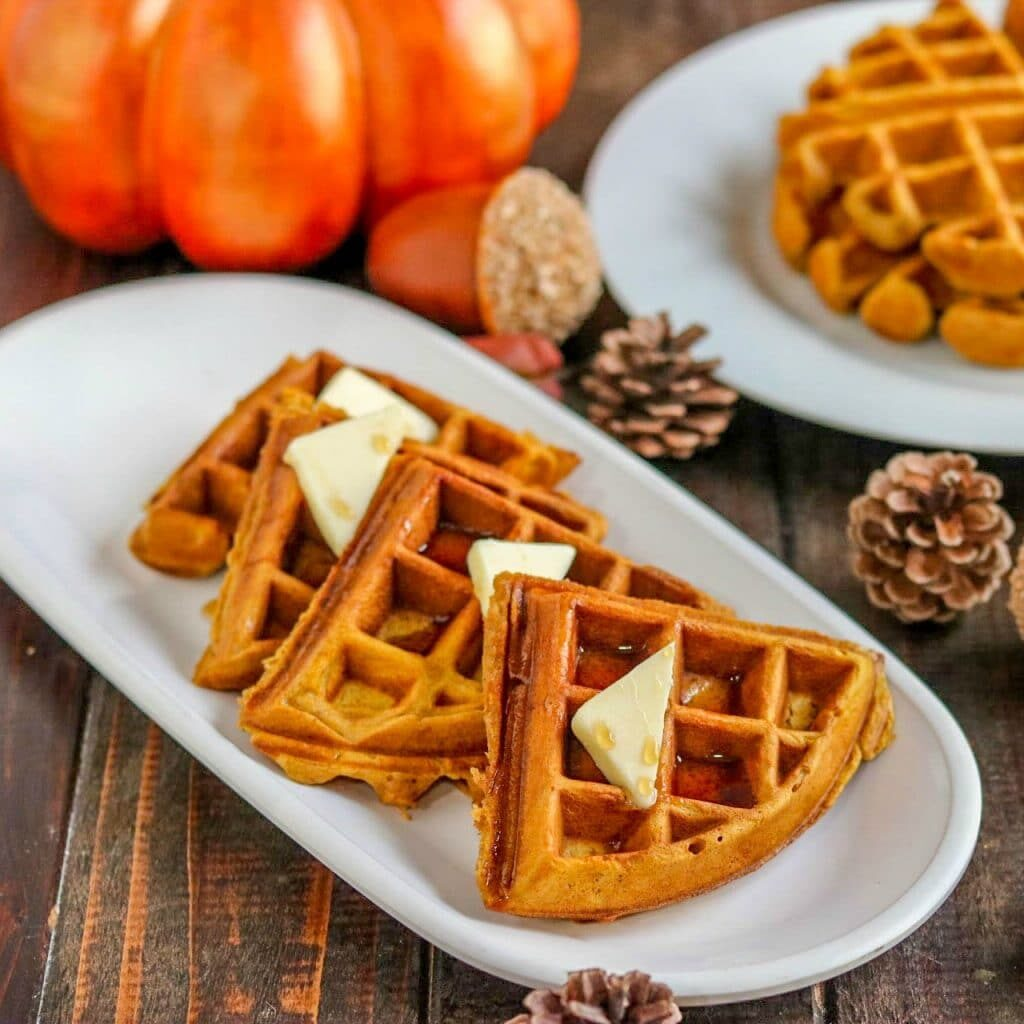 Pumpkin spice waffle wedges topped with butter and syrup on white plate with pumpkin, decorative acorn, pine cones, and another white plate with whole waffles on wood table.