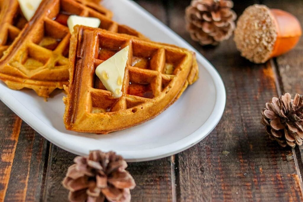 Closeup of wedges of pumpkin spice waffles topped with butter and syrup on white plate surrounded by pine cones and decorative acorn on wood plate.