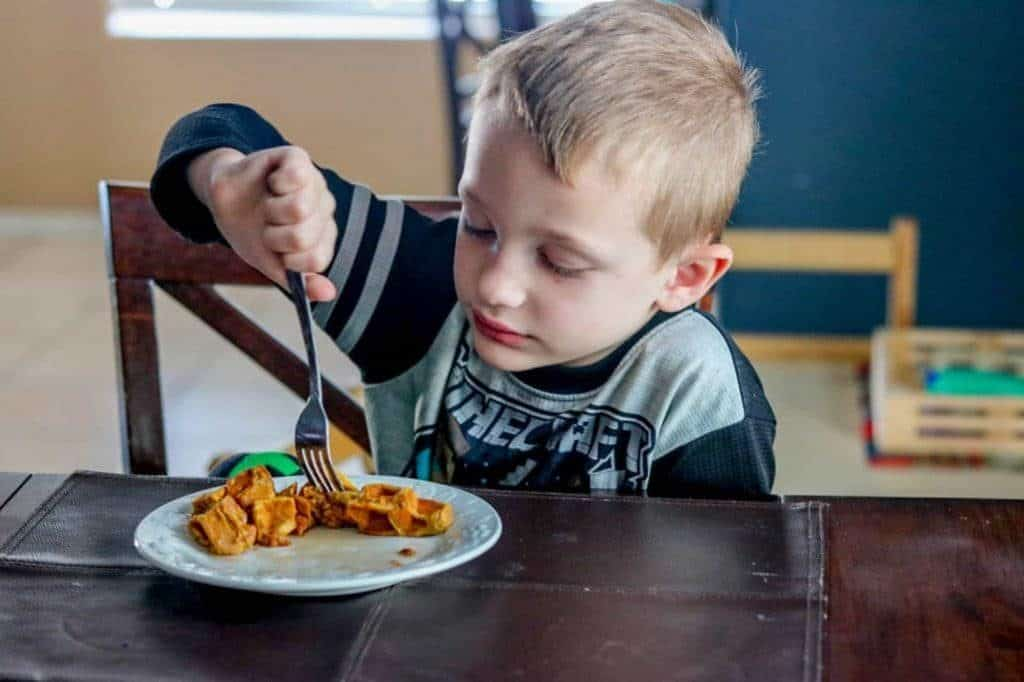 Child eating pumpkin spice waffle on white plate with fork.