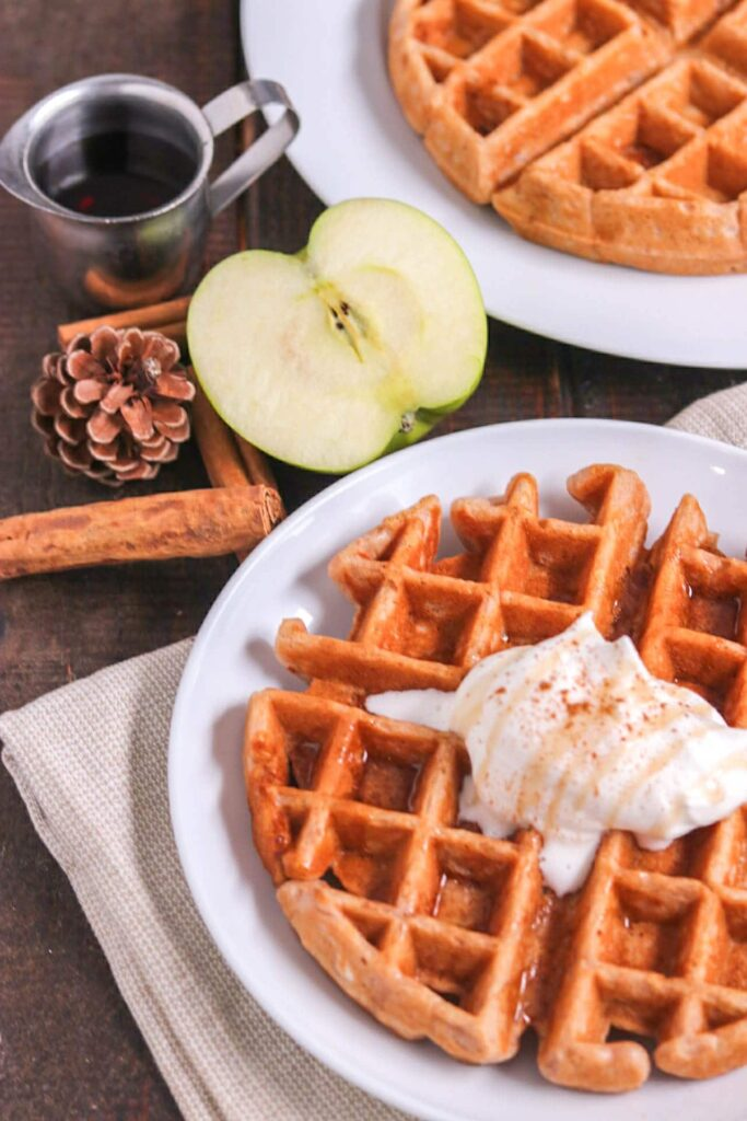apple cinnamon waffle with whipped cream, a cut apple and pinecone