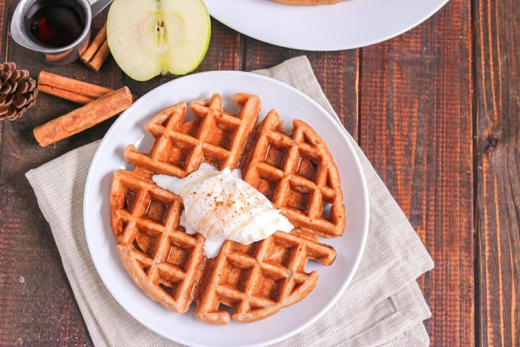 Overhead shot of apple cinnamon waffle topped with whipped cream on white plate with cinnamon sticks, half an apple, and syrup cup on the side on wood table.
