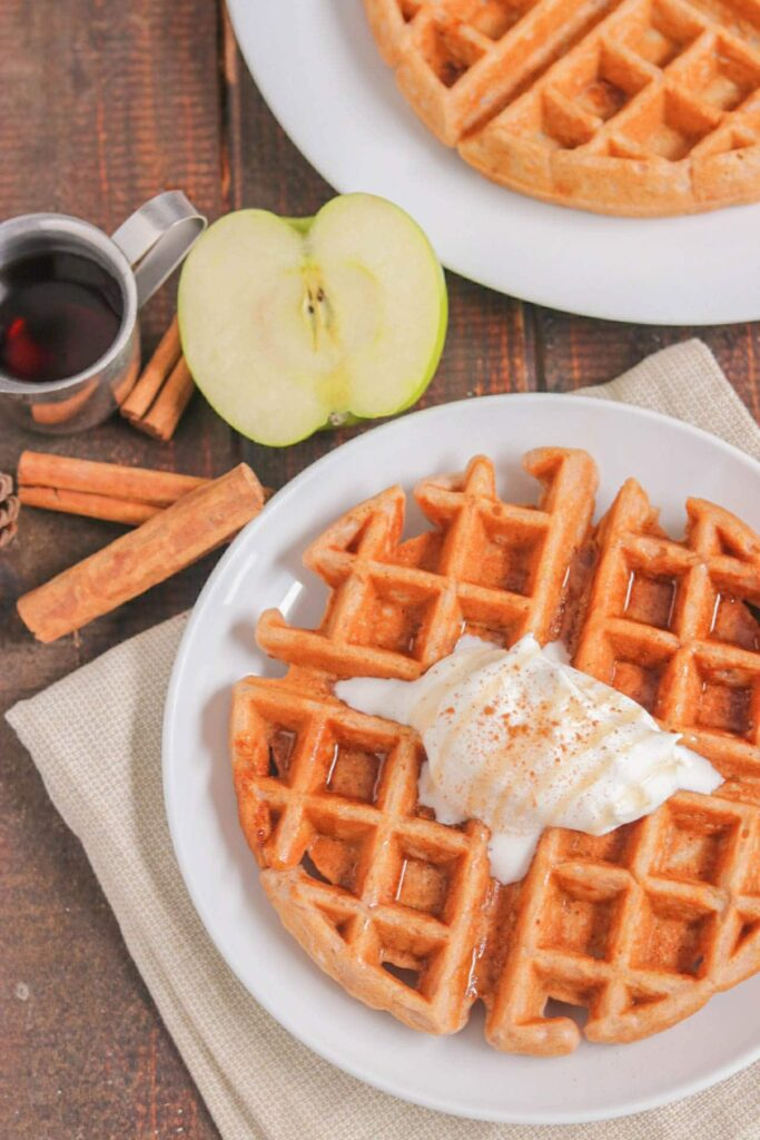 Overhead shot of apple cinnamon waffle topped with whipped cream on white plate with cinnamon sticks, cup of syrup, and half an apple on the side on wood table.
