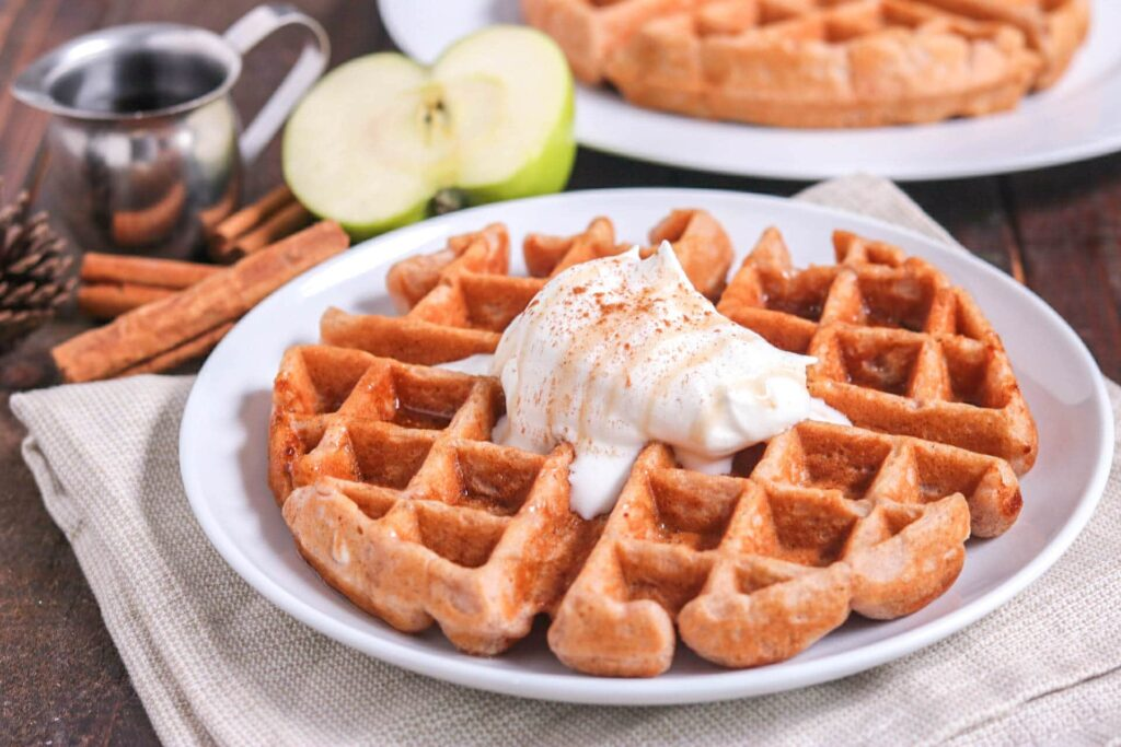 Closeup of apple cinnamon waffle topped with whipped cream on white plate with half an apple, cinnamon sticks, and syrup cup in background on wood table.