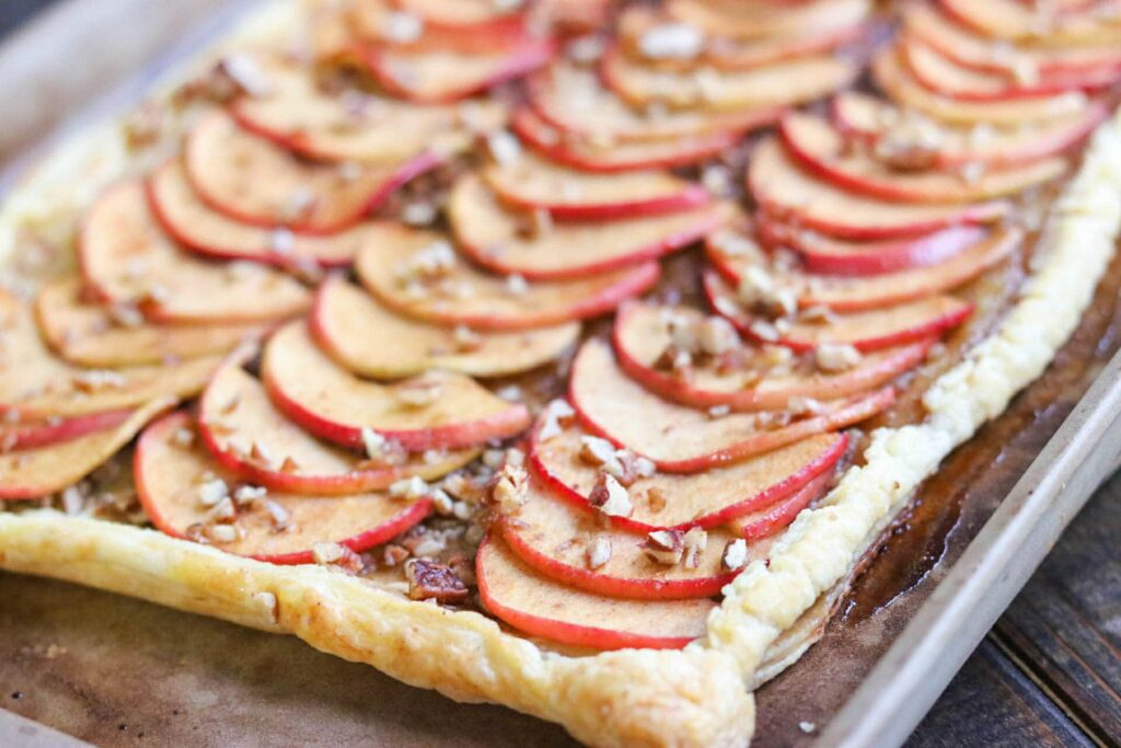 Baked pecan apple tart on metal baking sheet.