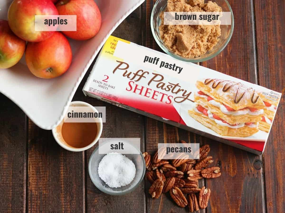 Puff pastry tart ingredients laid out on a wooden board for a puff pastry apple tart