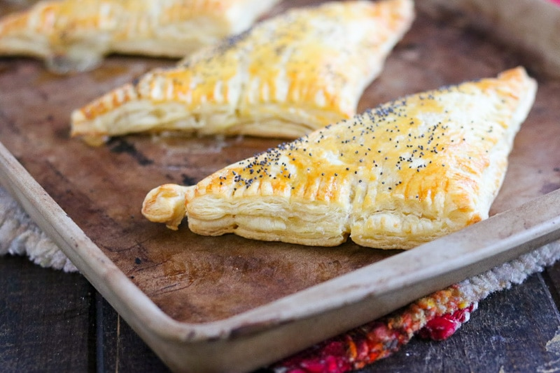 Chicken and rice turnovers in metal baking tray on wood table.