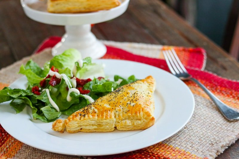 Chicken and rice turnover with salad on white plate on tweed mat with more turnovers on white serving dish in background on wood table.