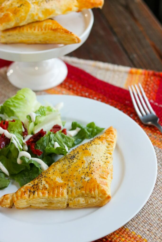 Chicken and rice turnover with salad on white plate with more turnovers in background on white serving dish.