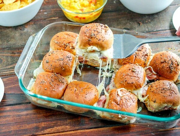 Spatula holding ham and pineapple slider with remaining sliders in glass baking dish beneath on wooden table.